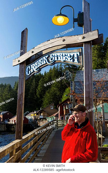 Man on a cell phone near the Creek Street sign and boardwalk, downtown Ketchikan, Southeast Alaska, USA, Spring