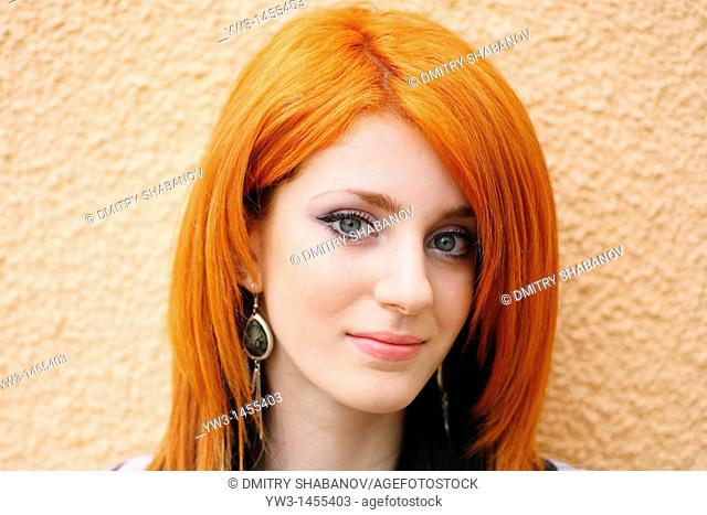 redhead women outdoors agains painted wall