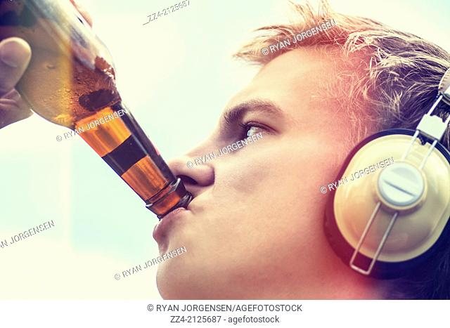 Close-up headshot of a young man drinking beer from glass bottle while listening to stereo headphones. Beer songs concept