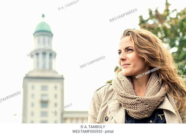 Germany, Berlin, smiling blond woman looking at distance