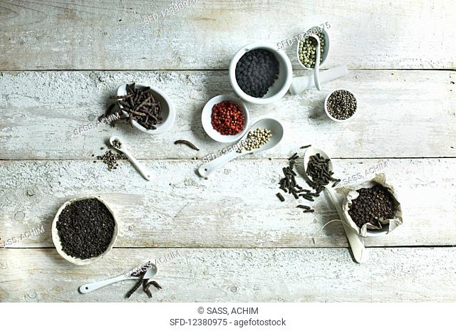 Different types of pepper on spoons and in small bowls