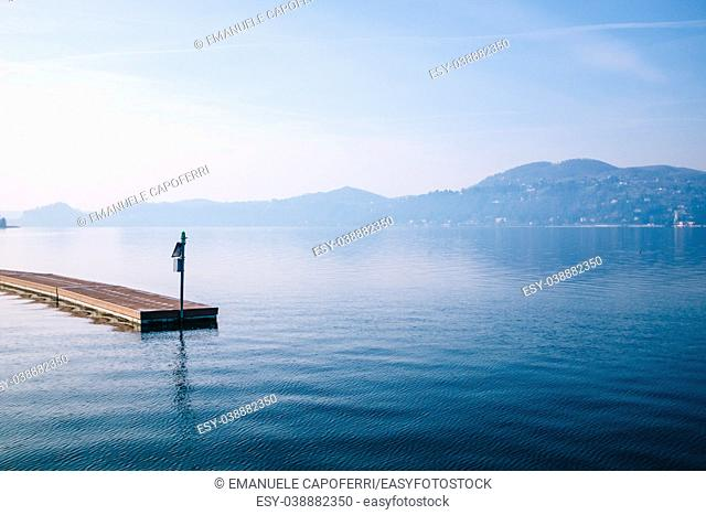 floating jetty with background the lake and mountains on a bright morning, Ranco, Lombardy, Lake Maggiore, Italy