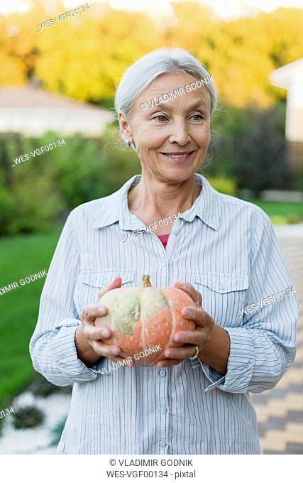 Portrait of smiling senior woman with harvested pumpkin in the garden
