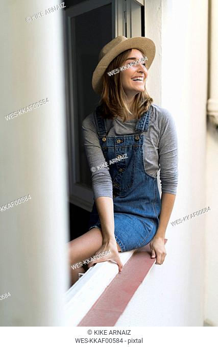Happy young woman sitting in window frame