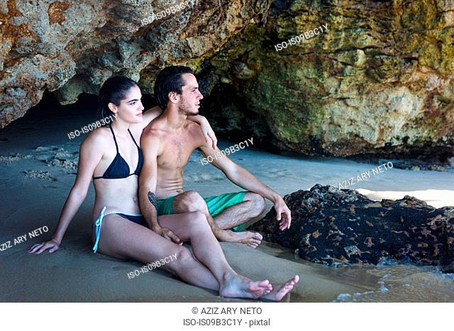 Young couple looking out from beach cave, Taiba, Ceara, Brazil