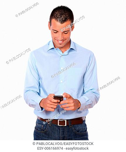 Portrait of a handsome adult male on blue shirt and jeans texting with his cellphone while standing on isolated background