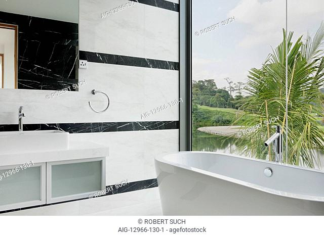 Marble and glass walls in modern bathroom with view to golf course