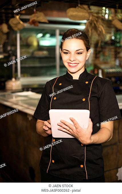 Smiling waitress in bar with digital tablet