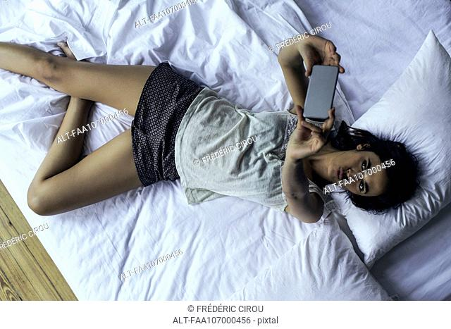 Woman lying on bed taking selfie with smartphone