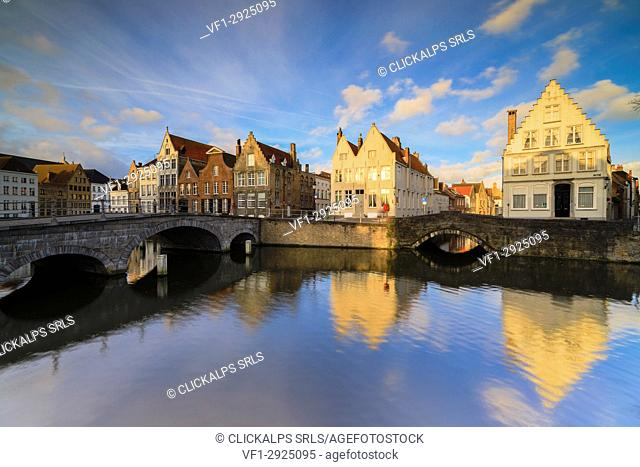 First lights of sunrise on the historic buildings and bridges reflected in the typical canal Bruges West Flanders Belgium Europe
