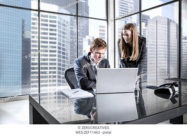 Businessman and woman in meeting discussing in office, using laptop