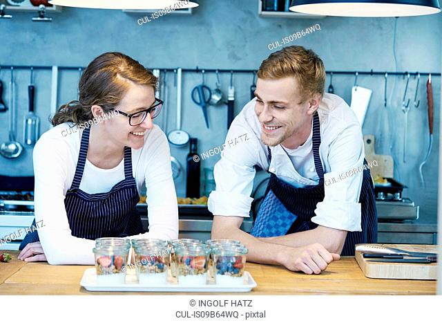 Two chefs, looking at tray of finished berry desserts, smiling