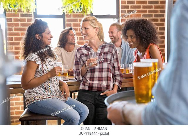 Group Of Female Friends Socializing In Bar Together