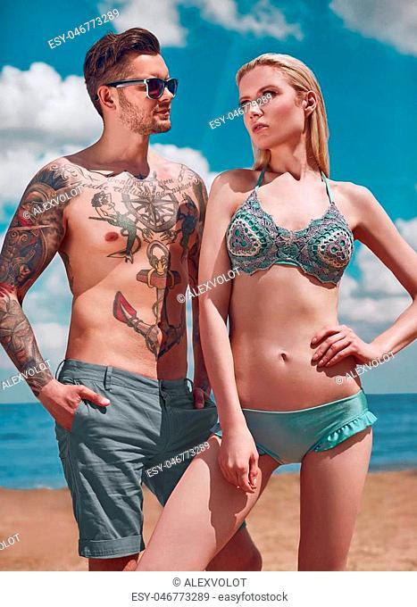 Fashion beautiful couple getting a suntan on the beach in resort