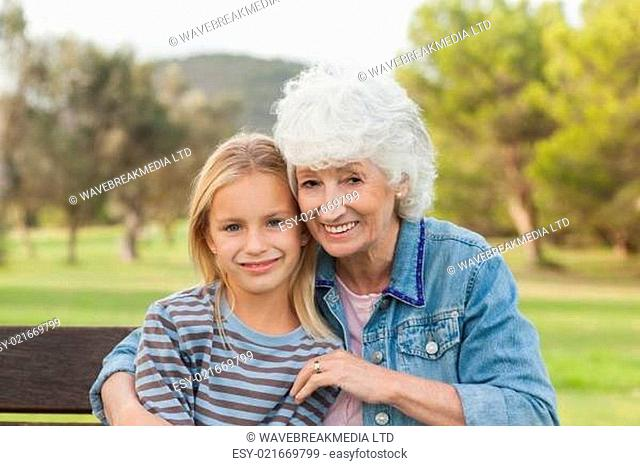 Little girl smiling with her grandmother sitting on park bench portrait
