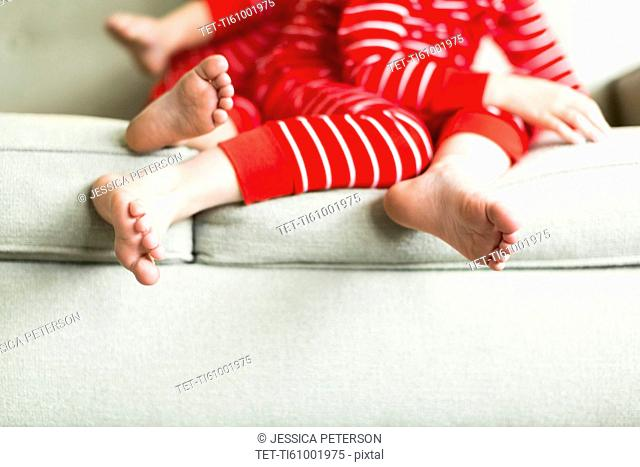 Feet of siblings (2-3, 4-5) in red pajamas