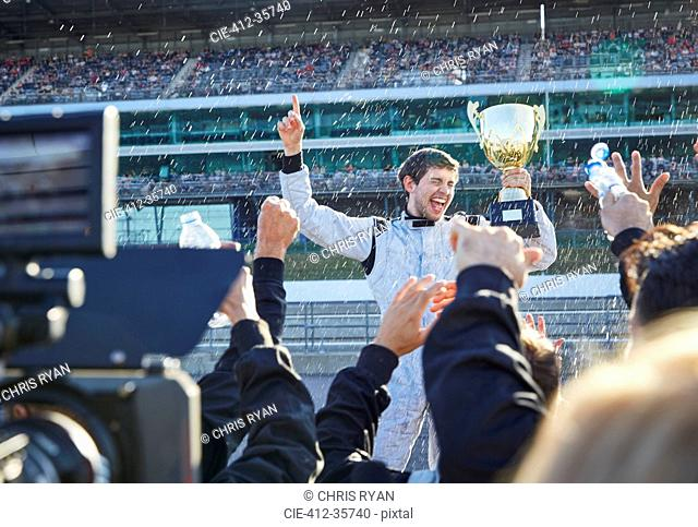 Formula one racing team spraying champagne on driver with trophy, celebrating victory on sports track