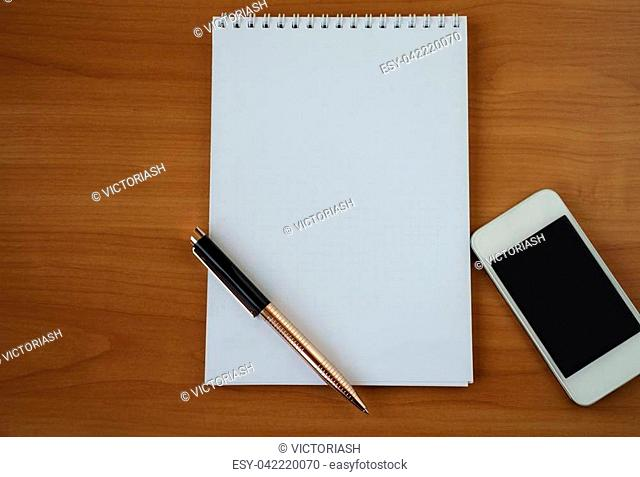 white paper notepad for notes with pen and phone on bright wooden background, closeup