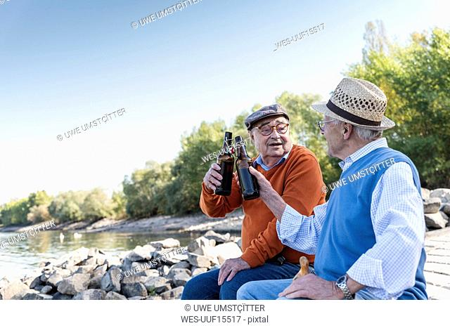 Old friends sitting by the riverside, drinking beer