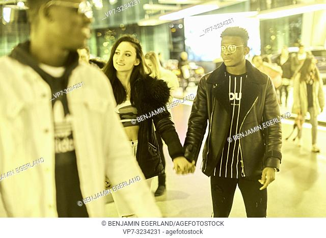 couple walking together in shopping mall, happy enjoying togetherness, in Munich, Germany