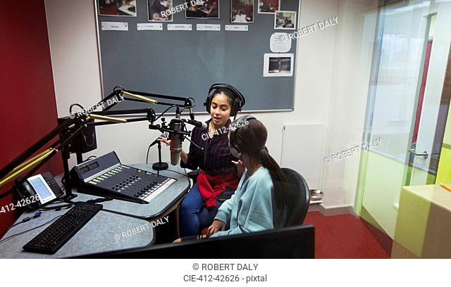 Teenage girl musicians recording music, singing in sound booth