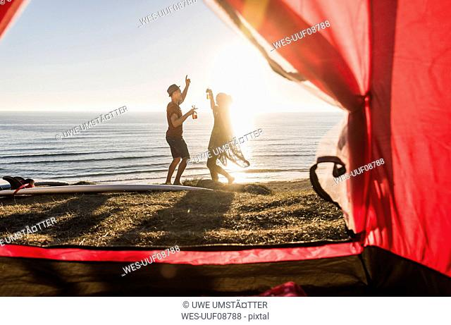 Dancing young couple camping at seaside