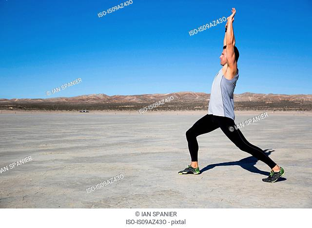 Man training, stretching with arms raised on dry lake bed, El Mirage, California, USA