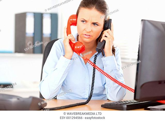 A businesswoman is telephoning with two devices in an office