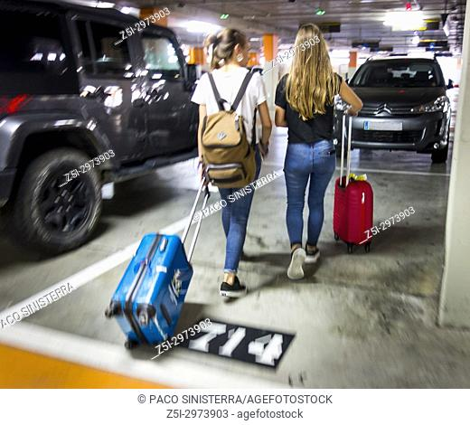 Girls with suitcases in parking, after arrival at Valencia airport, Spain