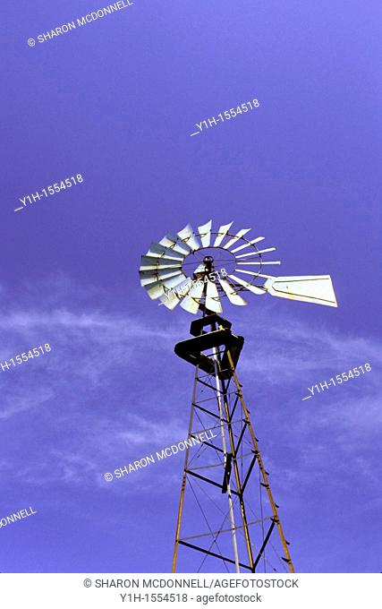 Antique Aermotor Farm style windmill for pumping water sits against a blue sky, midwest USA
