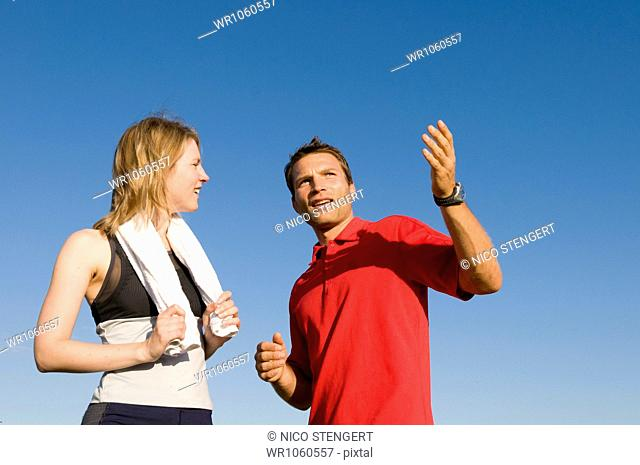 Woman working with personal trainer outdoors