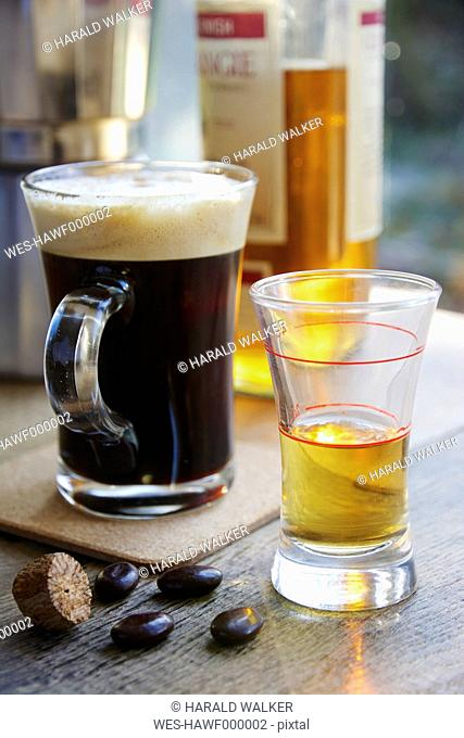 Cup of fresh coffee and a shot glass with whisky for marking Irish Coffee