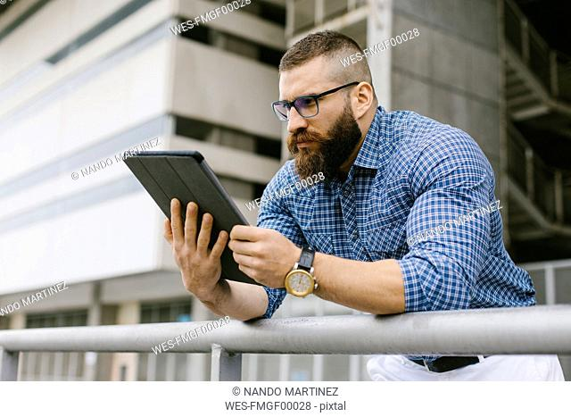 Bearded hipster businessman wearing glasses, wrist watch and plaid shirt using digital tablet