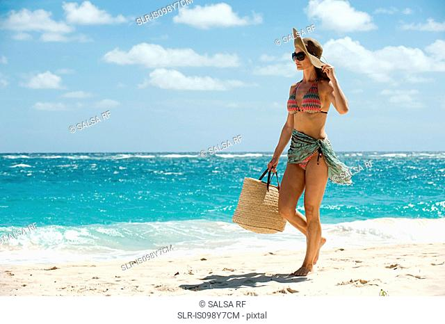 Woman walking on sandy beach, Mustique, Grenadine Islands