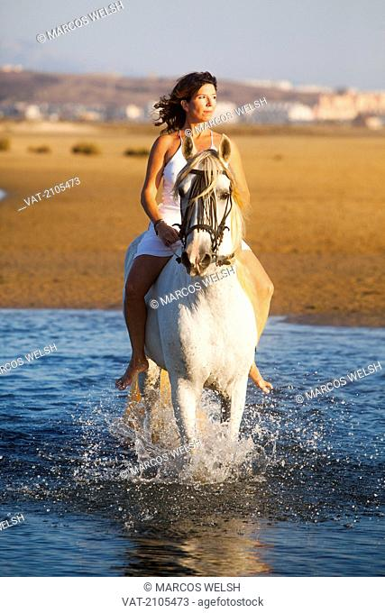 A woman riding a white horse into the water, tarifa cadiz andalusia spain