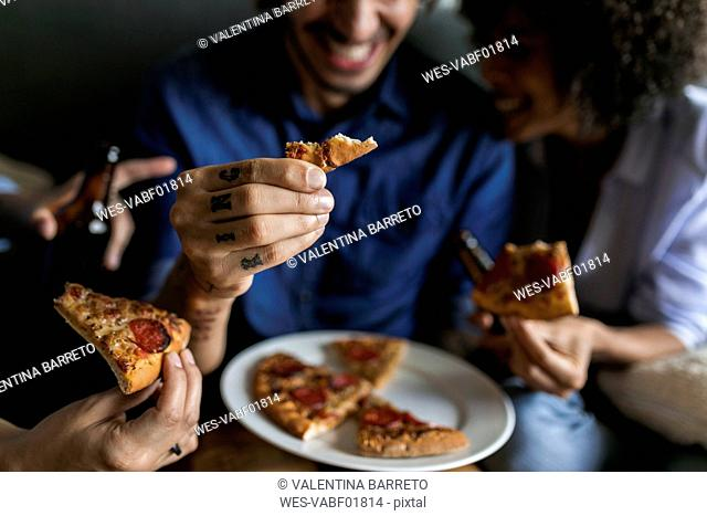 Close-up of tattooed man with friends holding pizza slice