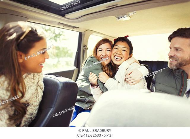 Enthusiastic female friends hugging in back seat of car