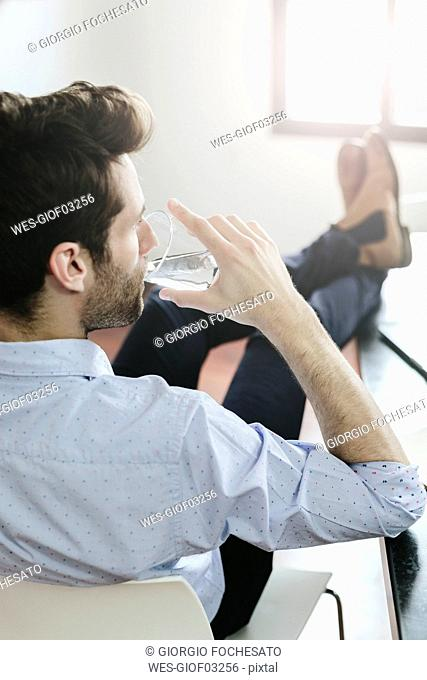 Young businessman working in office, drinking water