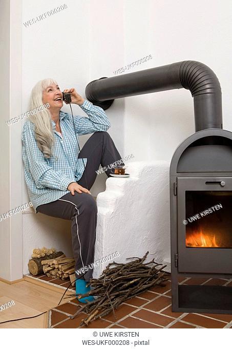 Germany, Duesseldorf, Woman talking on phone near fireplace