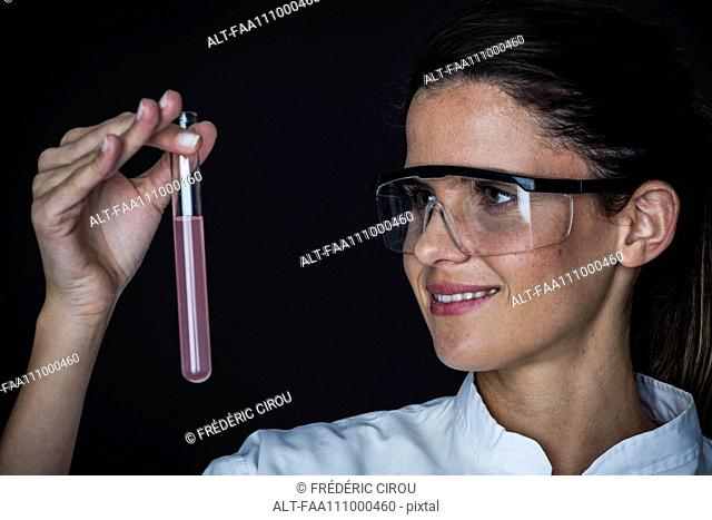 Young woman looking at liquid in test tube