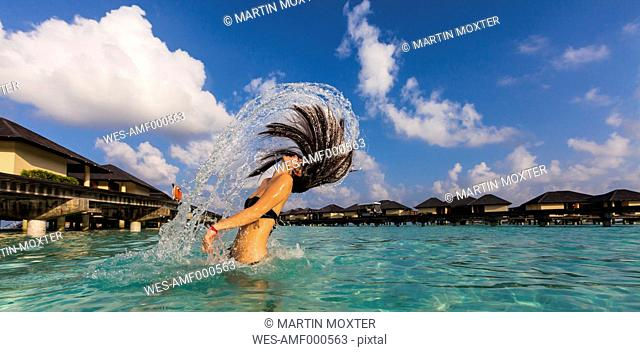 Maldives, Young woman splashing wet hair in lagoon
