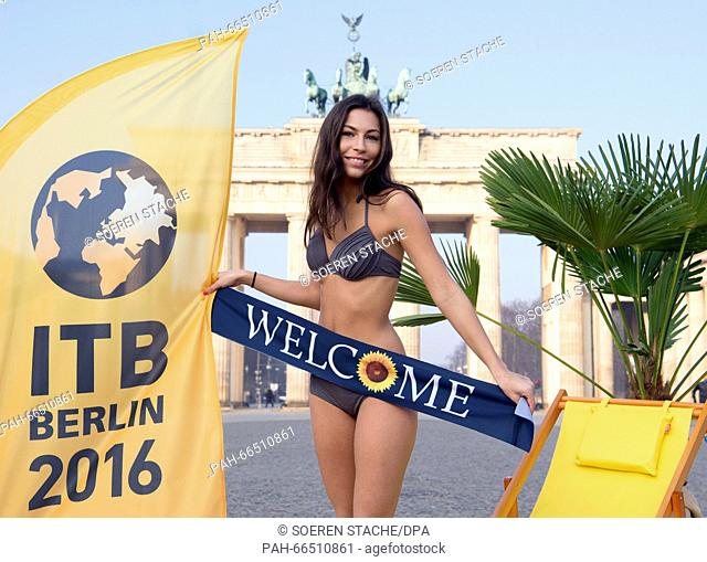 Model Amy wearing a bikini and a sash that reads 'Welcome' poses next to a flag featuring the logo of the Internationale Tourismus-Boerse (ITB, lit