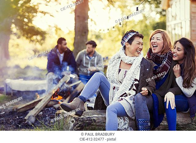 Female friends laughing and roasting marshmallows at campfire