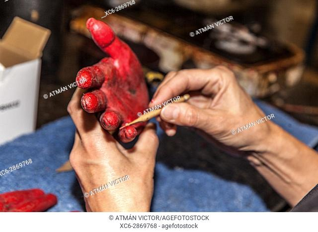 artisan in a workshop painting on a red sculpture