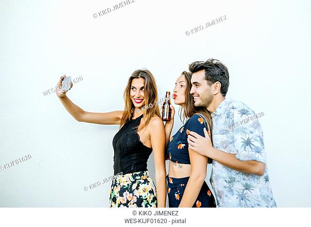 Friends taking a selfie with smartphone in front of white wall