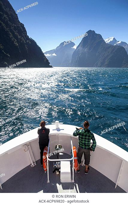 Tourists on the bow of a tour boat on Milford Sound in front of Mitre Peak in Fiordland National Park, New Zealand