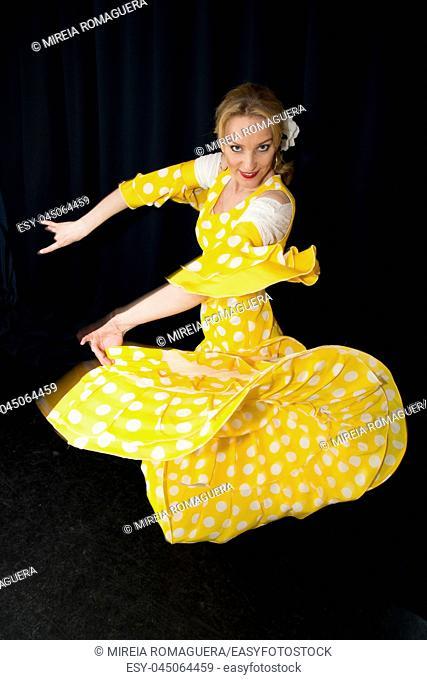 Flamenco dancer dressed in yellow wavin her dress