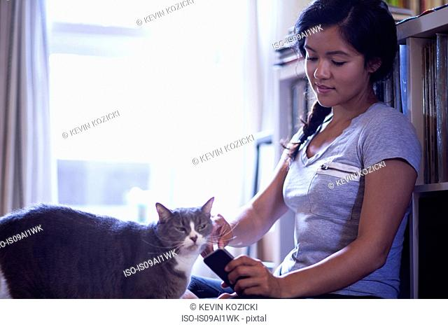 Young woman holding cellular phone stroking cat