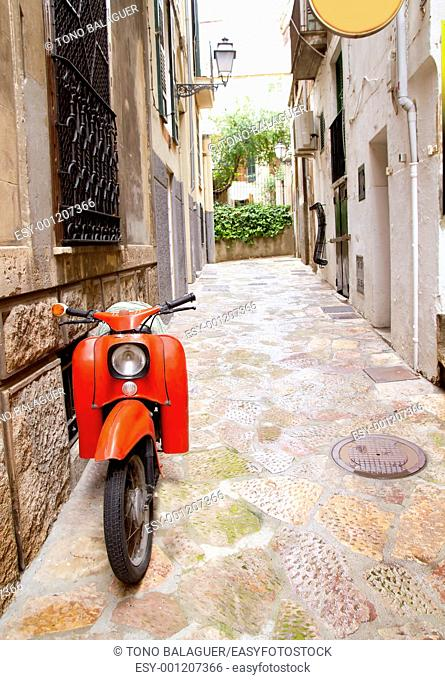 Mediterranean street with old retro red scooter in Palma de Mallorca Spain
