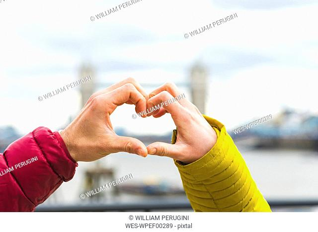UK, London, hands of young couple in love forming heart, close-up